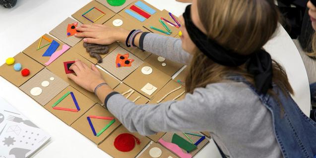 Una nena, jugant amb el joc de memòria tàctil.