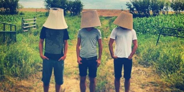Retrat dels músics Adam Basanta, Julian Stein i Max Stein amb pantalles de làmpades al cap