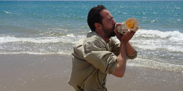 Fotografía de un señor soplando una caracola de mar