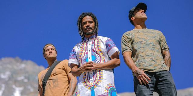 Els tres membres de la banda vestits amb camises de colors vius i retratats contra un cel d'un blau intens