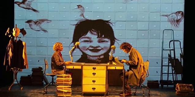 Escena de la obra, dos actores en una mesa escritorio