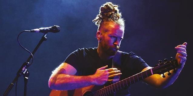 Retrat del cantautor amb el cabell recollit sobre el cap i tocant la guitarra