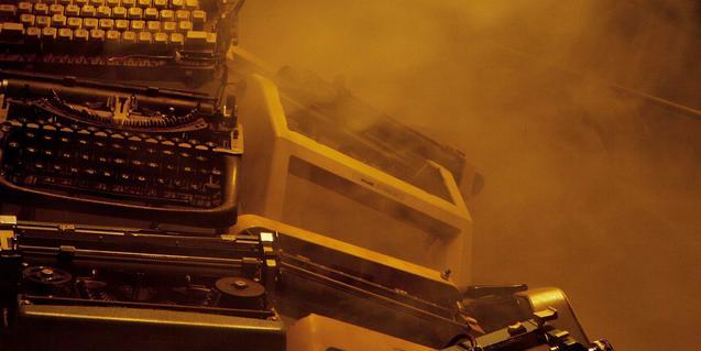 Unes màquines d'escriure antigues apilades entre núvols de fum
