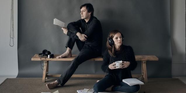 Un actor i una actriu de la companyia amb un llibre a la mà i amb auriculars per escoltar música posats