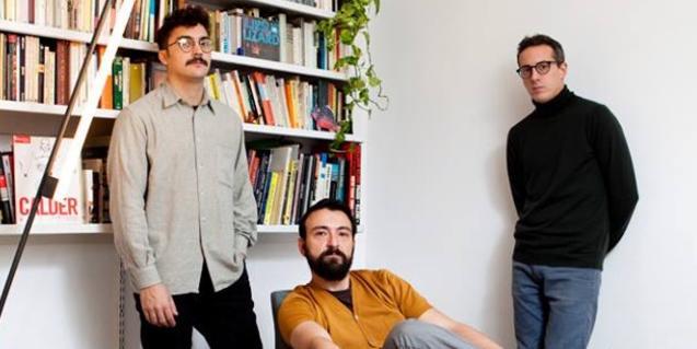 Los tres integrantes de la banda retratados ante una estantería llena de libros