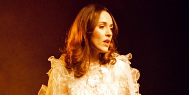 La artista retratada con el cabello largo y con un traje blanco de blonda