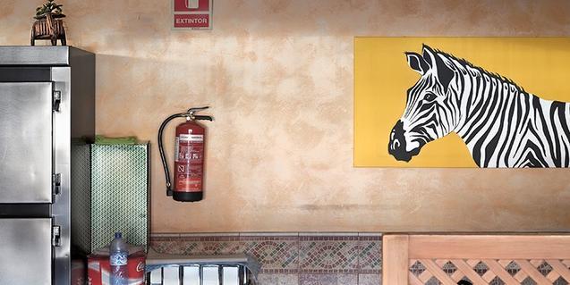 Una de las fotografías de la exposición muestra el interior de un bar con un extintor y un cuadro de una cebra