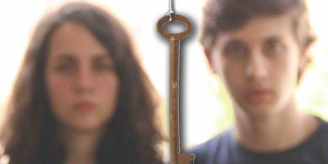 Retrato de los jóvenes protagonistas desenfocados y con una llave en primer plano entre ambos