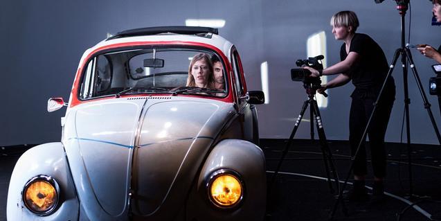Un momento de la representación con los actores dentro de un coche y un cámara filmándolos
