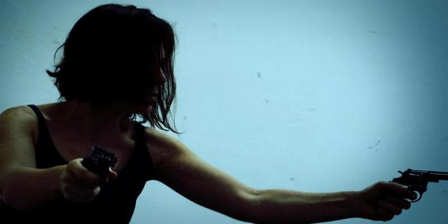 Una de les actrius de la funció, en penombra i amb una pistola a cada mà