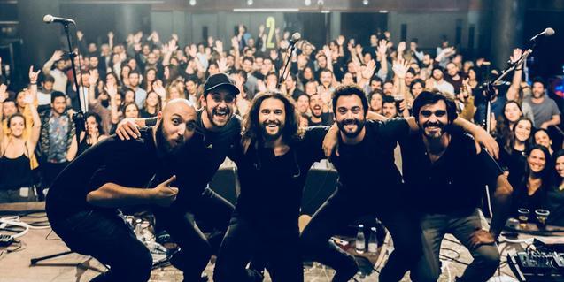 Els integrants de la banda fent-se una foto de grup a l'escenari amb el públic a l'esquena