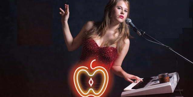 Retrat de la conductora de l'espectacle amb un vestit de festa i un neó amb forma de poma al davant