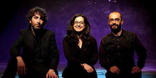 Retrato de los tres integrantes de la compañía sentados ante un fondo oscuro