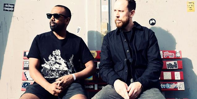 Els dos productors de música electrònica asseguts en un banc al sol