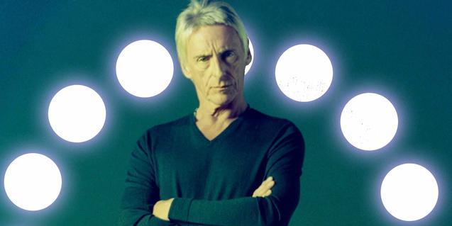 El músico con unas luces dispuestas en forma semicircular a su espalda