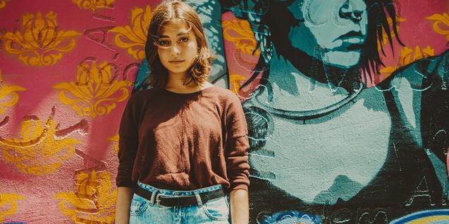 La artista retratada ante un muro con un grafiti