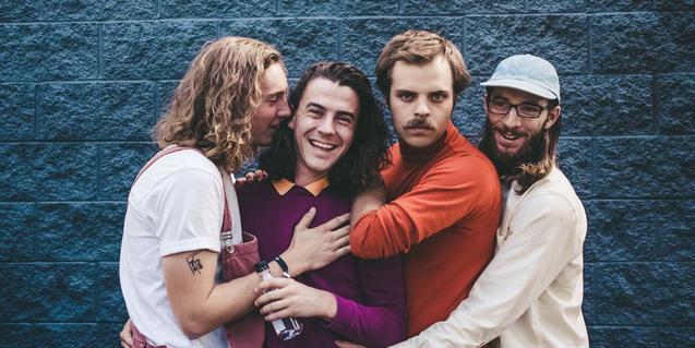 Els quatre membres de la banda retratats mentre s'abracen