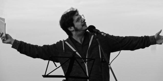 Retrat del poeta amb els braços oberts i mirant cap al cel
