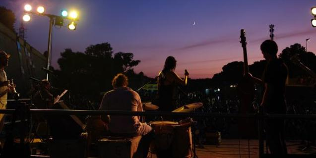 A group playing music at night at the Castell de Montjuïc.
