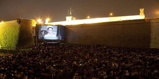 Screening of a film in the Castell de Montjuïc with lots of people watching it in the open air.