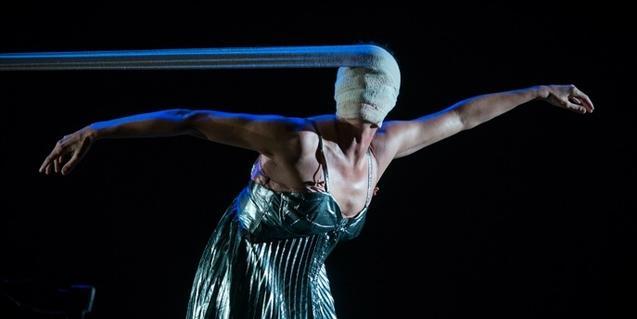 La bailarina y coreógrafa bailando con una pieza de tela que le cubre el rostro