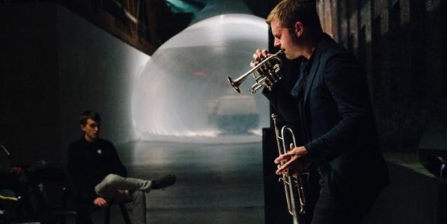 El trompetista Peter Evans tocando una trompeta y sosteniendo otra en la mano
