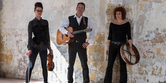 El músic australià, amb una guitarra a les mans i envoltant de dues col·laboradores