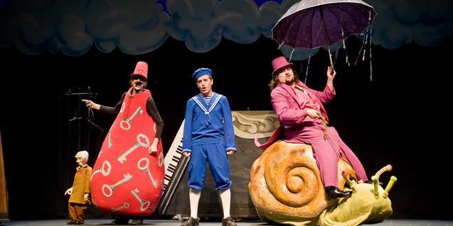 Fotografía del espectáculo con tres de los actores cantando en el escenario