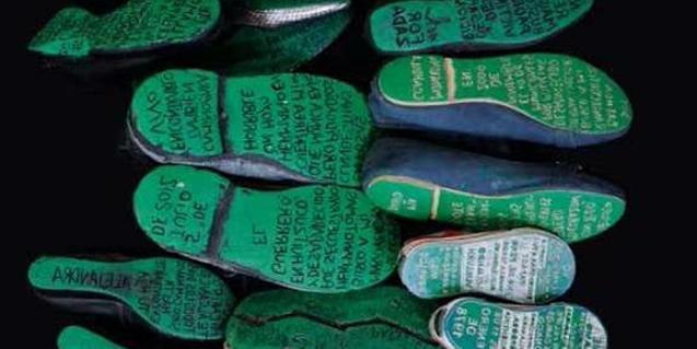 Fotografía de algunos de los zapatos que se pueden ver en la exposición con las suelas llenas de mensajes escritos