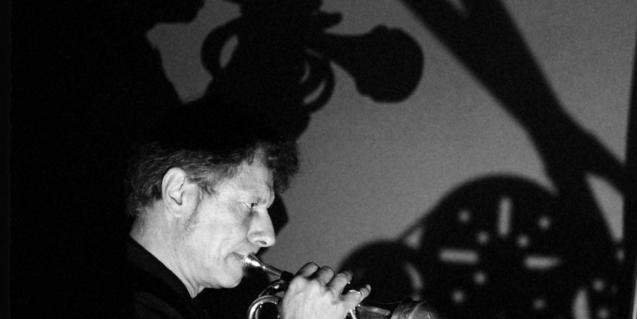 Retrato en blanco y negro del músico Pierre Bastien tocando una trompeta