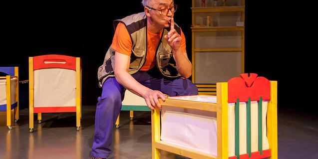 Fotografia de l'espetacle, el protagonista gronxant un bressol