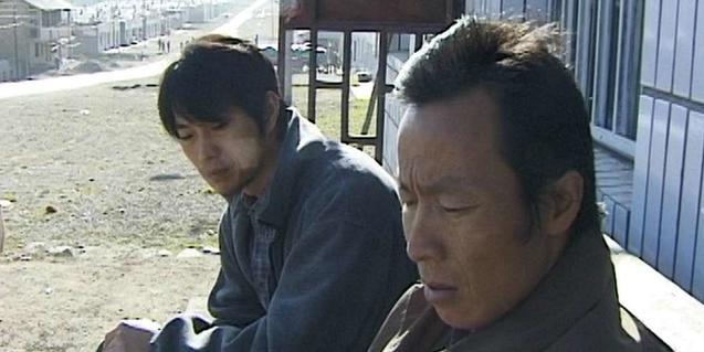 Una imagen del film con dos hombres chinos sentados en un banco