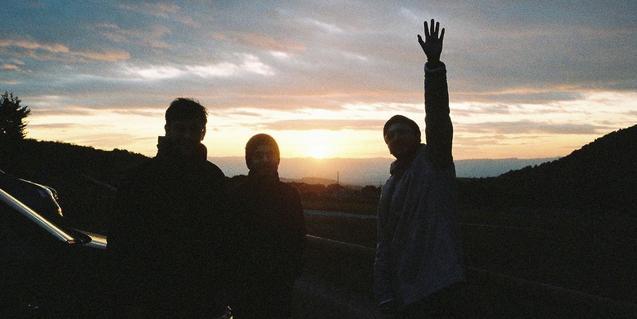 Els integrants de la banda retratats a contrallum amb una posta de sol al fons