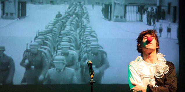 El protagonista de l'espectacle, amb nas de pallasso, davant d'una pantalla de projeccions