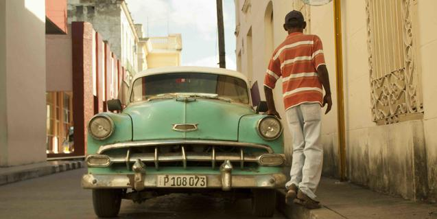 Un jove cubà d'esquenes passa al costat d'un cotxe dels anys 50