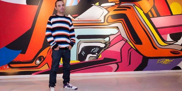 El grafitero PRO176 retratado en la Montana Gallery ante uno de sus murales