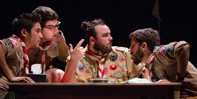 Fotografía de una escena del espectáculo, 4 de los protagonistas hablando en una mesa