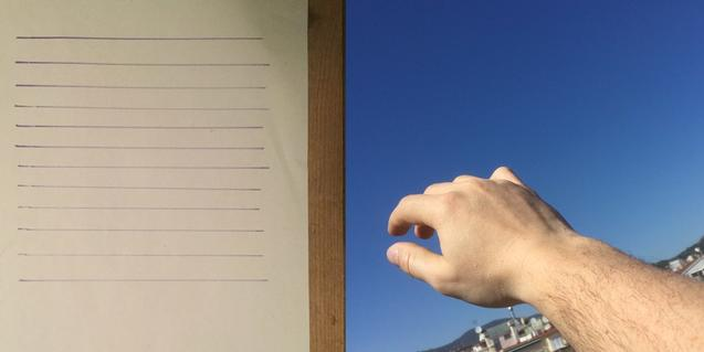 Una mano contra el paisaje de la ciudad y al lado de una hoja con una llista