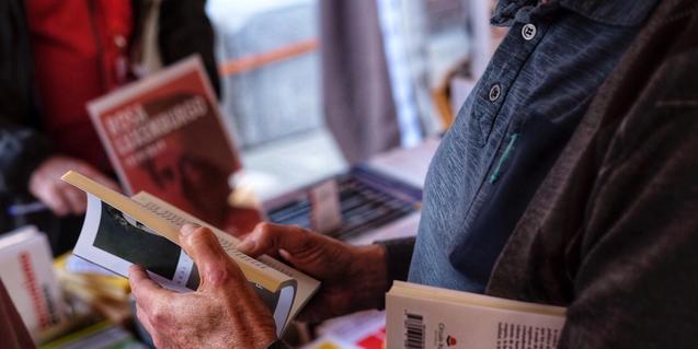 Una fotografia mostra unes mans d'home fullejant un llibre en una parada
