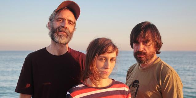 Tres dels integrants de la banda retratats davant del mar