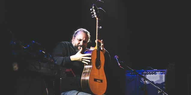 L'artista flamenc tocant la guitarra amb l'instrument en posició vertical durant una actuació