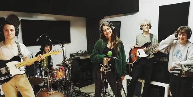 La banda retratada mentre enregistra una cançó a l'estudi