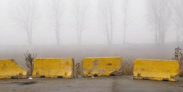 Una de les imatges de Jordi Comas que mostra unes tanques de carretera embolicades en boira i uns arbres de fons