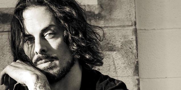 Retrato de primer plano del guitarrista con el cabello largo al viento