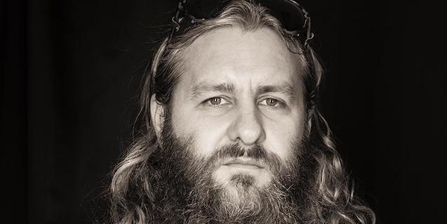 Retrato del músico australiano con el cabello largo y gafas de sol sobre la cabeza