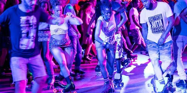 Un grupo de chicos y chicas bailan sobre patines