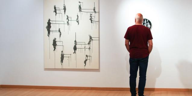 Un visitant es mira una de les obres de l'artista exposada al Piramidon