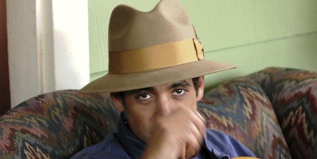 Retrat del músic, amb la mà a la cara i amb un barret al cap