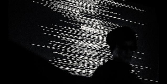 Imatge en blanc i negre que mostra el perfil de Ryoji Ikeda sobre un fons gràfic produït per ordinador