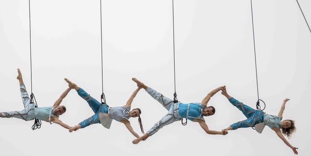 Una imagen del espectáculo aéreo que ofreció la compañía muestra a cuatro bailarines suspendidos de cables evolucionando en el vacío